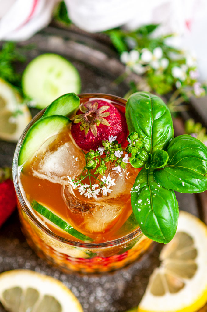 Classic Pimm's Cup Cocktail with lemon, cucumber, and strawberry slices garnished with basil leaves in glass over head view