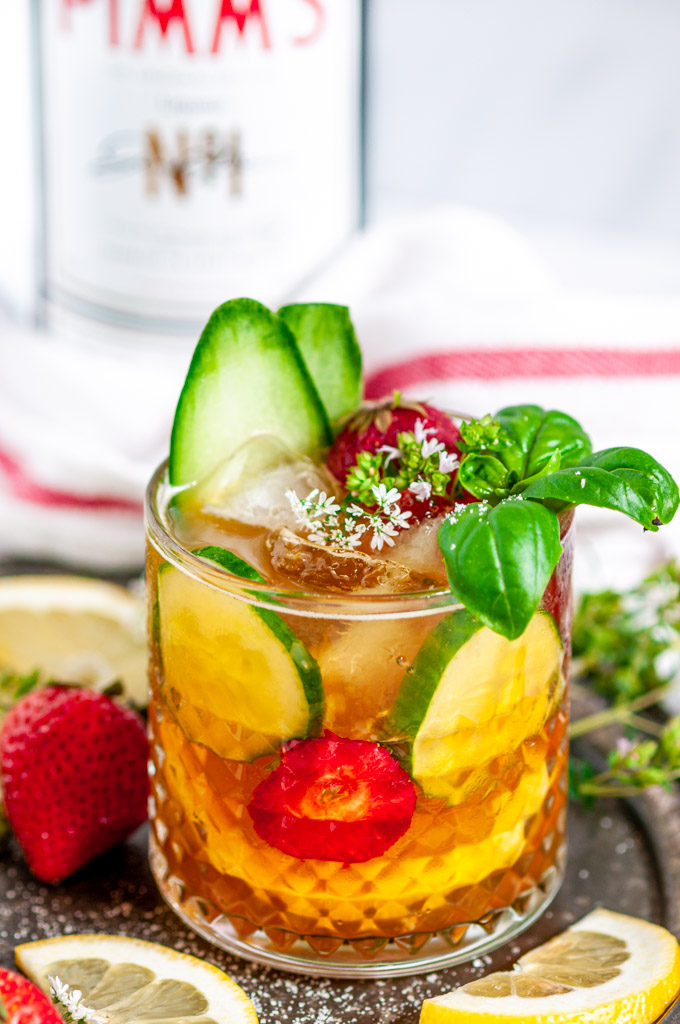 Classic Pimm's Cup Cocktail with lemon, cucumber, and strawberry slices garnished with basil leaves in glass side view close up