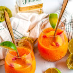 Frozen Peach Margaritas in glasses with lime slices and gold stirrers on white marble with tea towel and tequila bottle in background