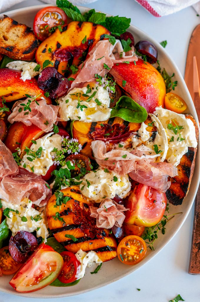 Grilled Nectarine Burrata Prosciutto Salad one ray plate with copper silverware over head