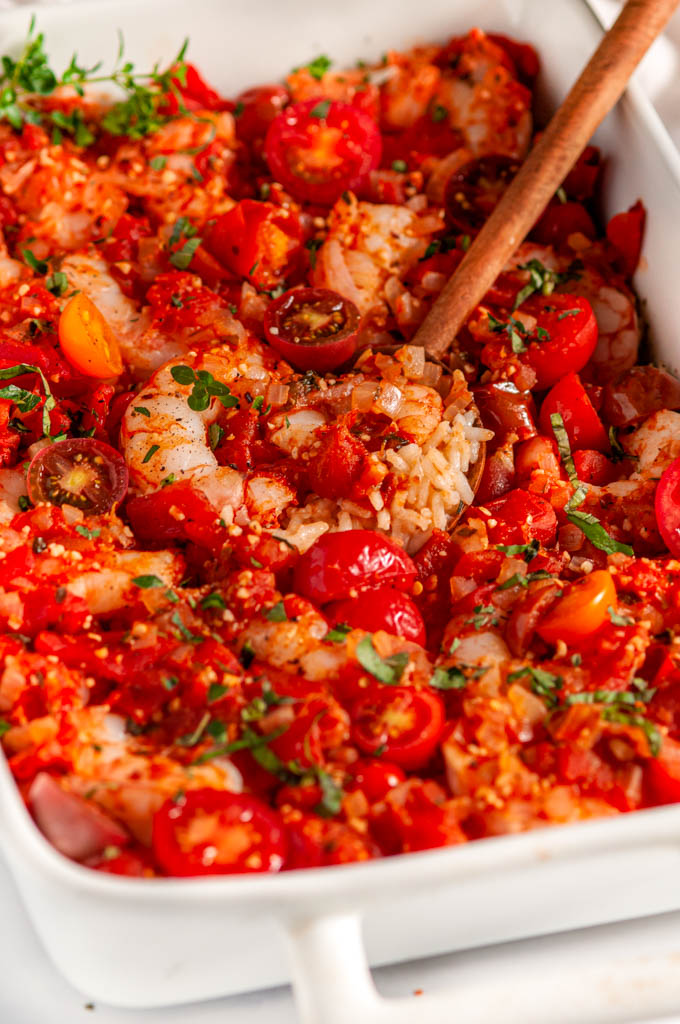 Healthy Italian Shrimp and Rice Casserole in white dish with tea towel and wooden spoon