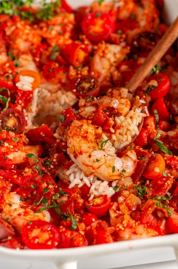 Healthy Italian Shrimp and Rice Casserole in white dish with tea towel and wooden spoon close up