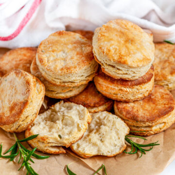 Leftover Sourdough Starter Rosemary Biscuits stacked with tea towel on parchment