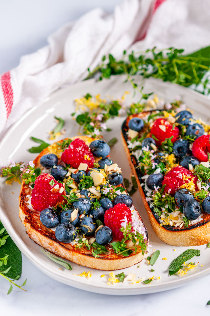 Lemon Berry Breakfast Toast with fresh herbs on gray plate with tea towel over head view