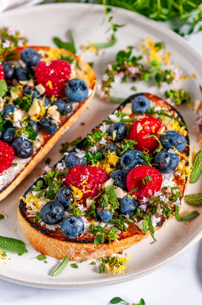 Lemon Berry Breakfast Toast with fresh herbs on gray plate with tea towel over head view close up