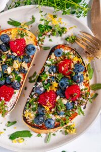 Lemon Berry Breakfast Toast with fresh herbs on gray plate with tea towel and gold utensils over head view close up