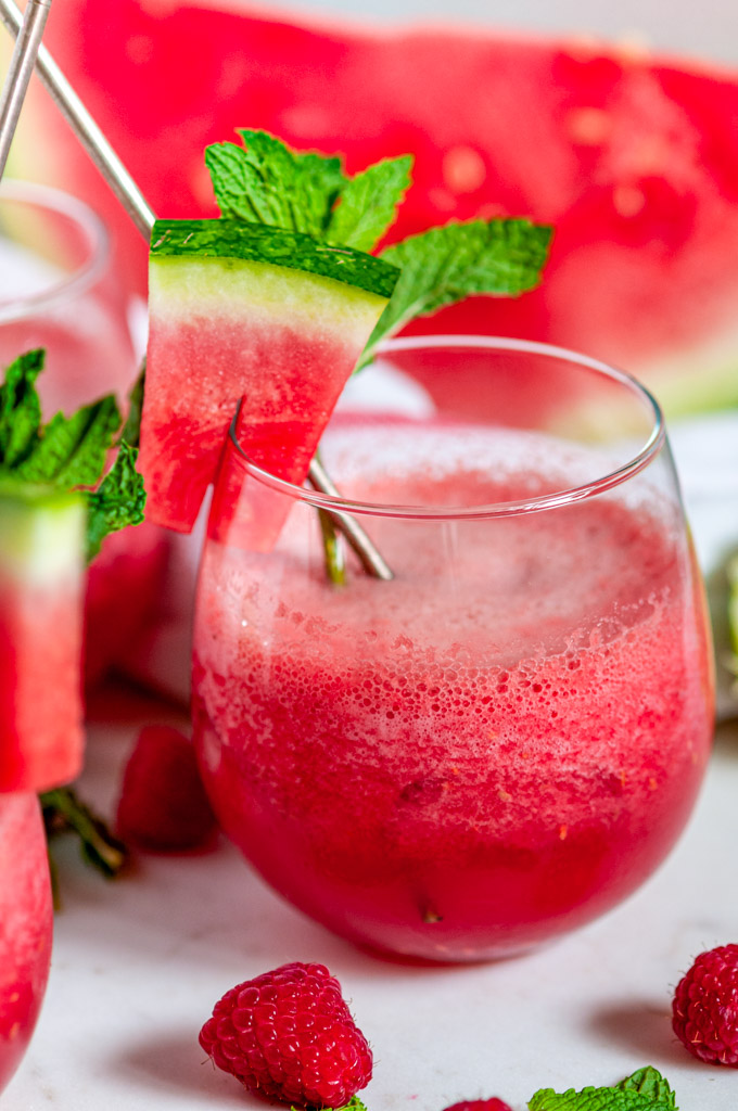 Sparkling Watermelon Raspberry Slushie Cocktail (Pitcher Recipe) in stemless wine glasses on white marble side view close up