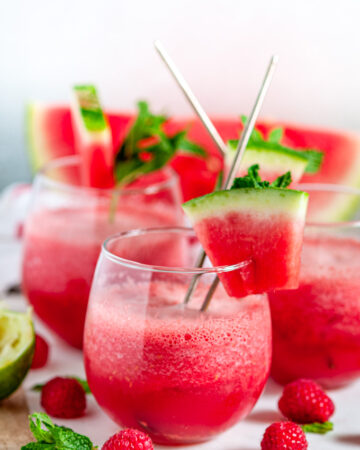 Sparkling Watermelon Raspberry Slushie Cocktail (Pitcher Recipe) in stemless wine glasses on white marble side view