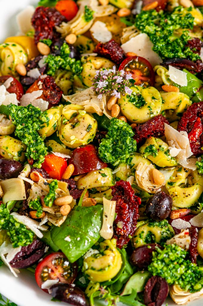 Tortellini Pesto Pasta Salad in white bowl with tea towel side view close up