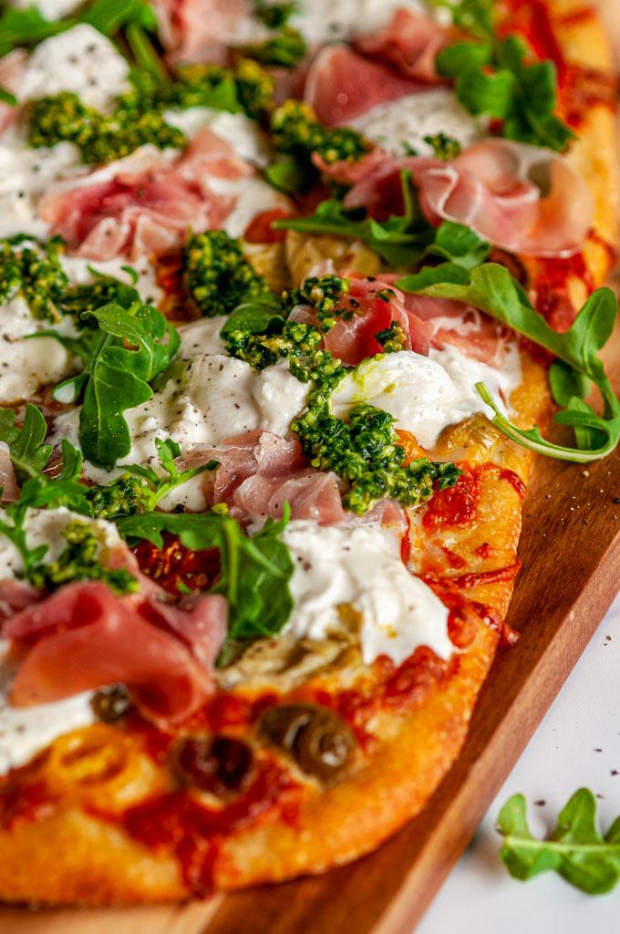 Mediterranean Prosciutto Burrata Flat Bread with arugula and pesto on wood pizza paddle close up