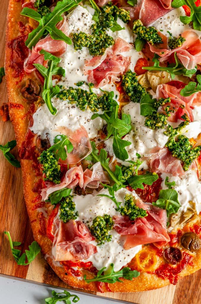 Mediterranean Prosciutto Burrata Flat Bread with arugula and pesto on wood pizza paddle