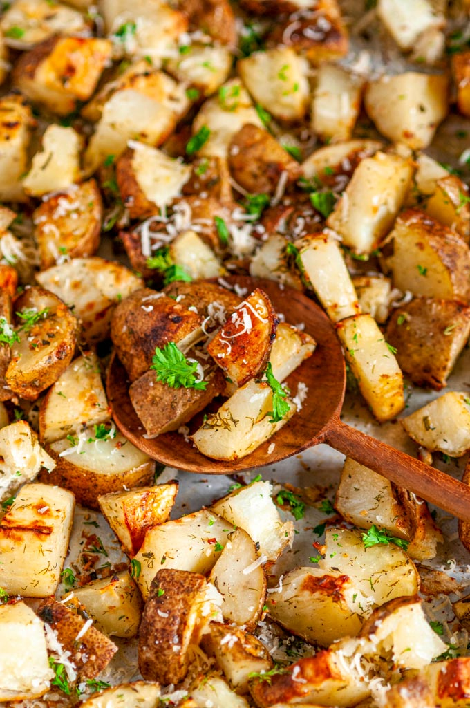 Parmesan Garlic Roasted Potatoes on sheet pan with wooden spoon close up
