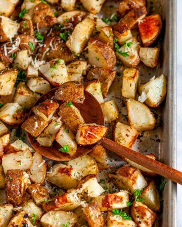 Parmesan Garlic Roasted Potatoes on sheet pan with wooden spoon