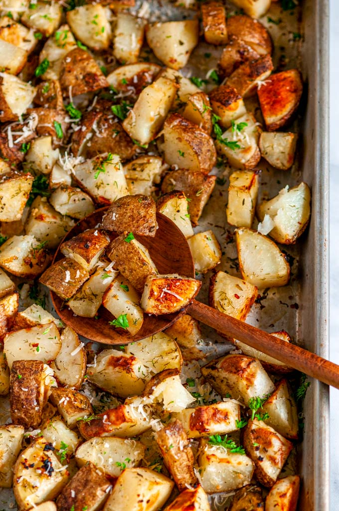 Parmesan Garlic Roasted Potatoes on sheet pan with wooden spoon