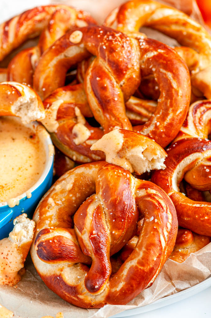 Pumpkin Beer Pretzels with Savory Pumpkin Cheese Dip on parchment paper and white marble close up