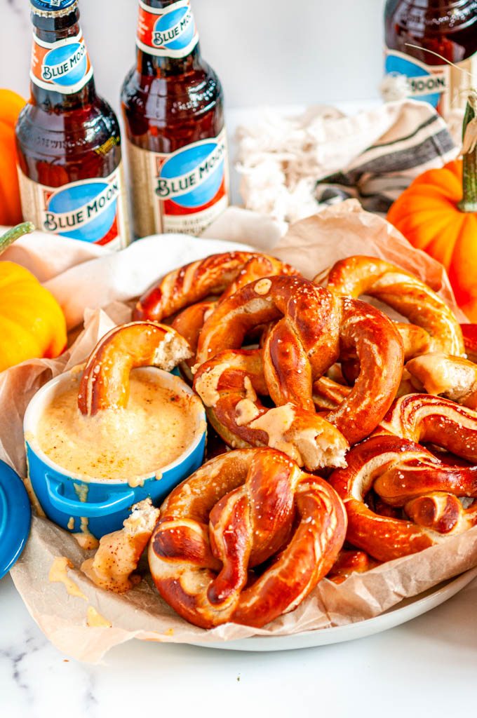 Pumpkin Beer Pretzels with Savory Pumpkin Cheese Dip on parchment paper and white marble