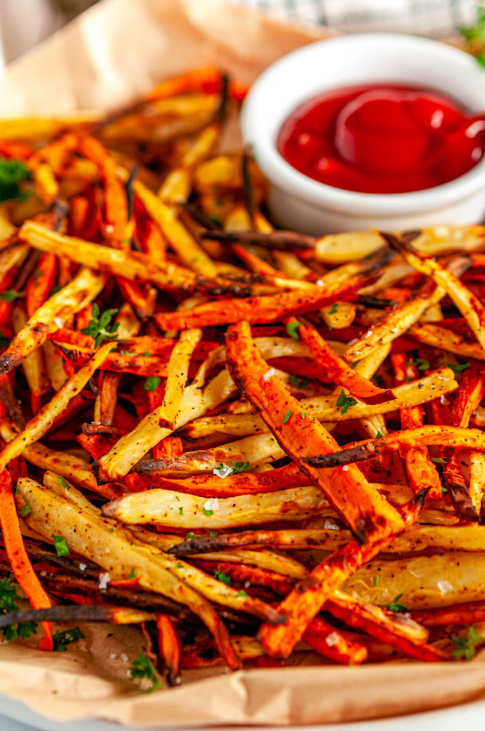 Sheet Pan Sweet Potato Fries with ketchup and parsley on brown parchment paper close up