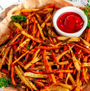 Sheet Pan Sweet Potato Fries with ketchup and parsley on brown parchment paper