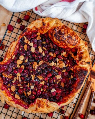 Autumn Cranberry Almond Galette on black wire rack with tea towel and copper silverware