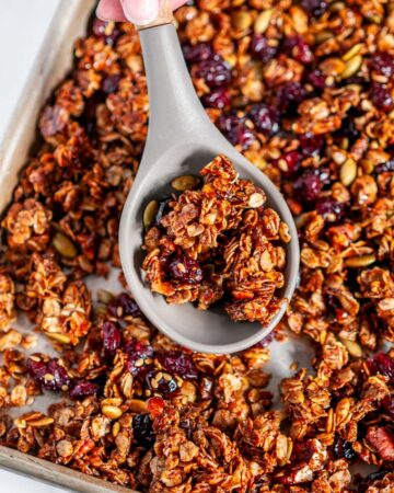 Chai Spice Cranberry Pecan Granola on sheet pan with gray silicone wooden spoon held in hand