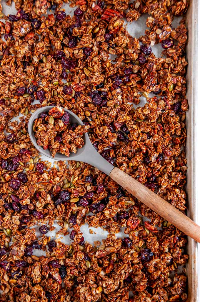 Chai Spice Cranberry Pecan Granola on sheet pan with gray silicone wooden spoon