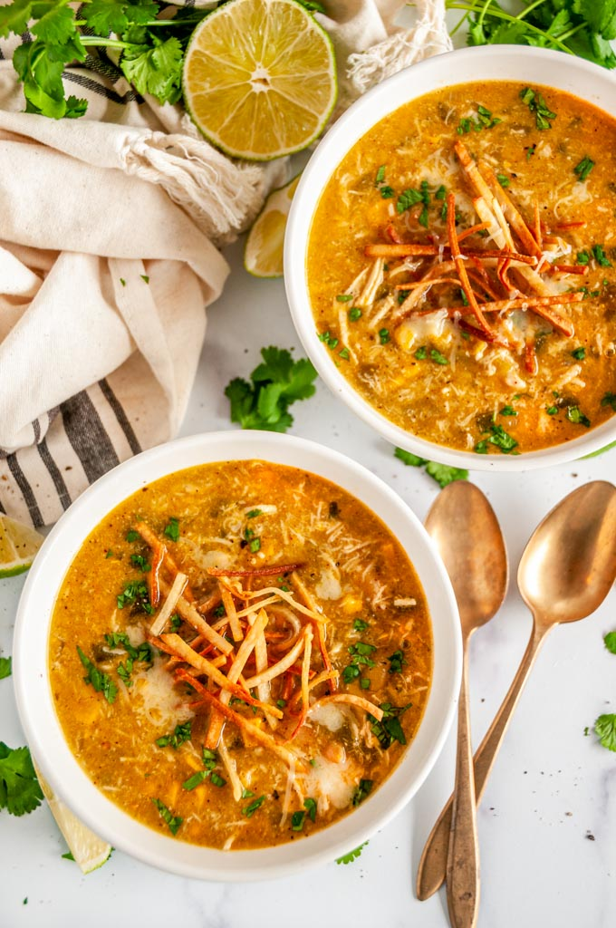 Instant Pot Green Chicken Enchilada Soup in white bowls with tortilla strips, limes and gold spoons on white marble