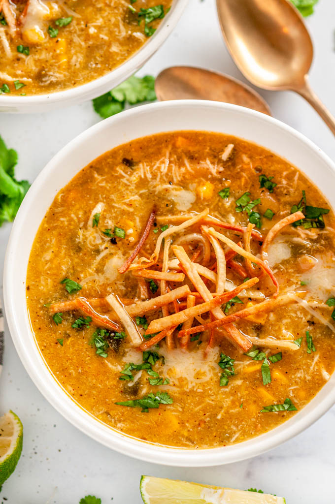 Instant Pot Green Chicken Enchilada Soup in white bowls with tortilla strips, limes and gold spoons on white marble close up