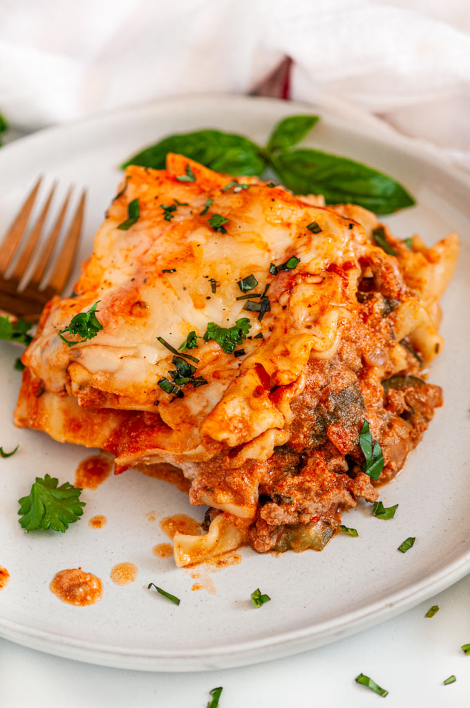 Instant Pot Turkey Vegetable Lasagna slice on white plate with gold fork and fresh basil