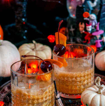 Pumpkin Bourbon Old Fashioned in whiskey glasses with Halloween Decorations