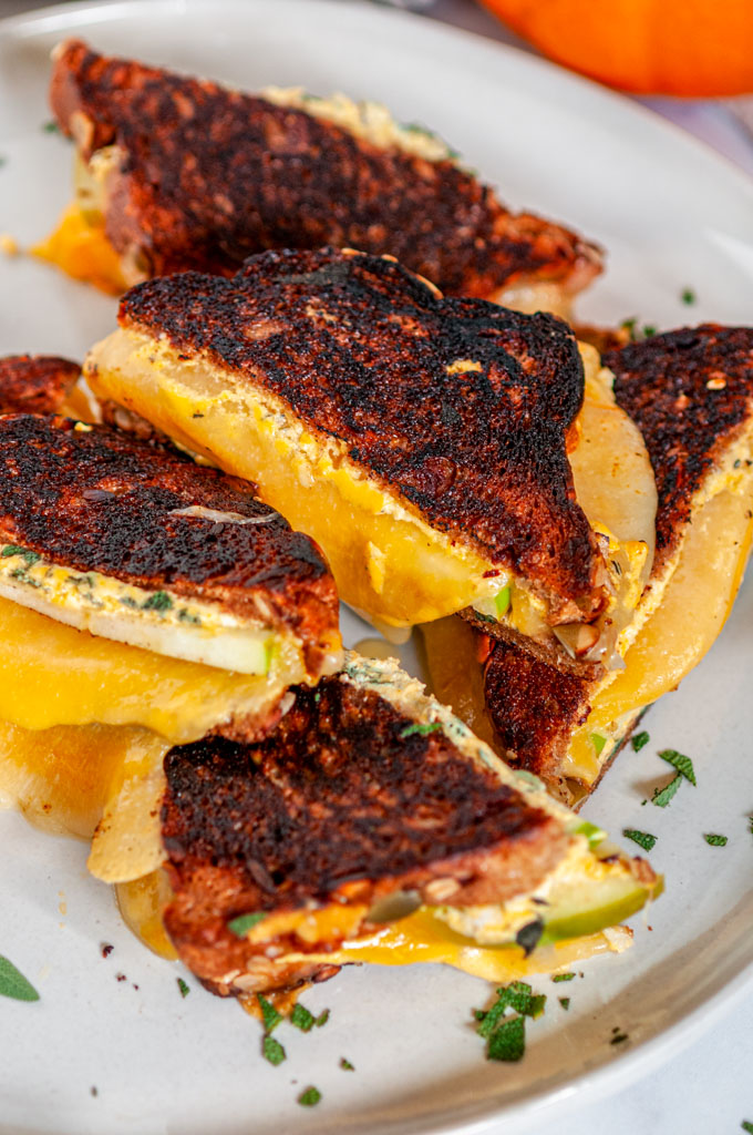 Pumpkin Grilled Cheese Sandwich on gray plate with apple slice and sage on white marble