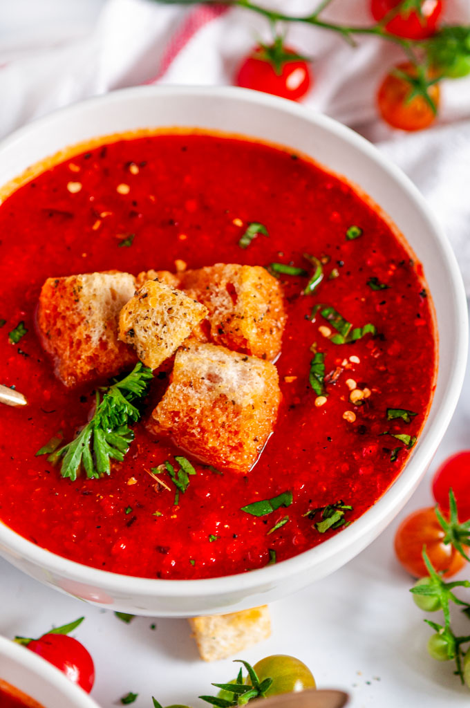 Roasted Bell Pepper Tomato Soup with croutons, parsley and gold spoon in white bowl