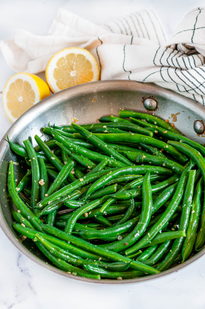 Easy Skillet Garlic Green Beans two images with blue rectangle and white text overlay in all-clad skillet with tea towel and lemons