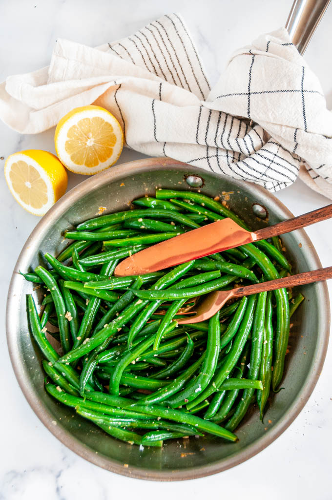 Easy Skillet Garlic Green Beans in all-clad skillet with copper silverware and lemons