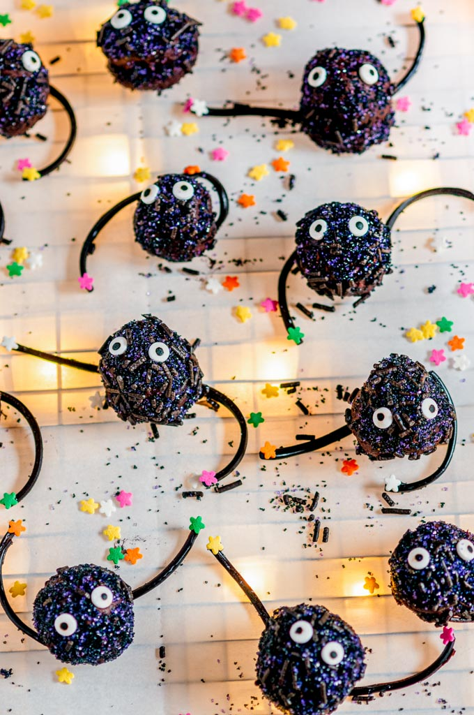 Soot Sprite Chocolate Truffles (Spirited Away) with colored star sprinkles on parchment backlit with twinkle lights