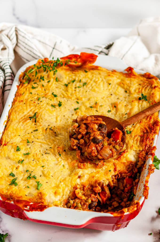 Vegetarian Shepherd's Pie in casserole dish with wooden spoon close up