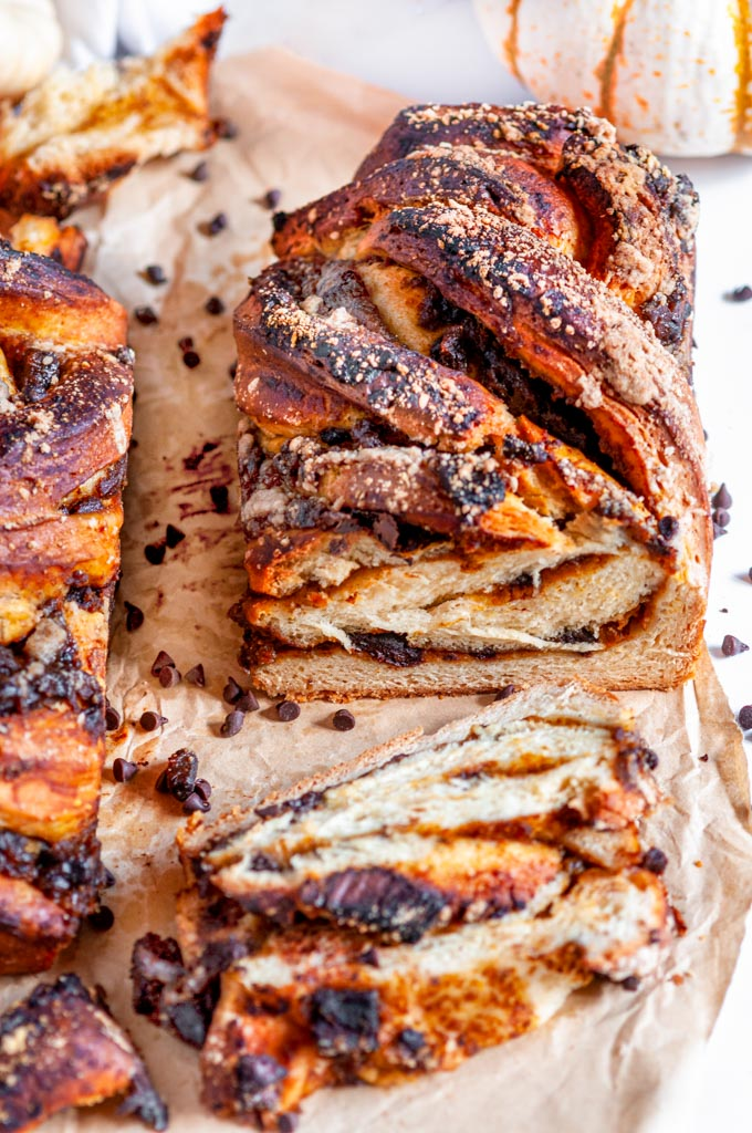 Chocolate Chunk Pumpkin Babka two loaves on sliced on parchment paper and white marble