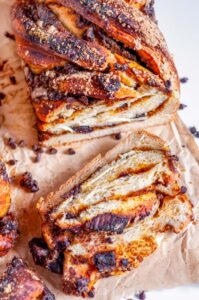 Chocolate Chunk Pumpkin Babka loaf sliced on parchment paper and white marble