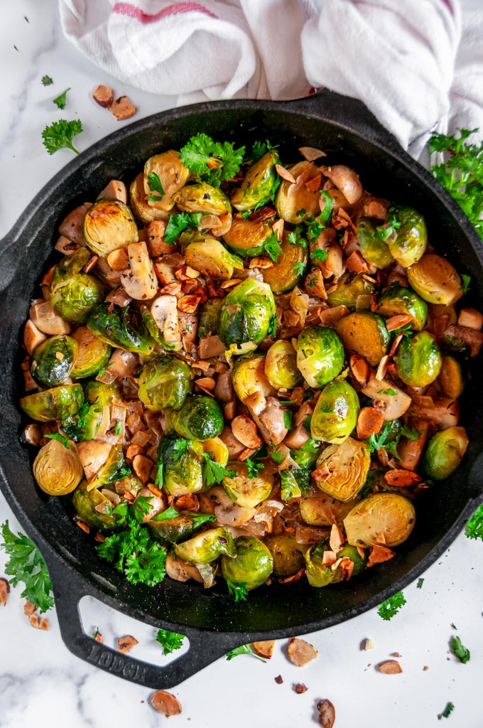 Creamy Skillet Brussels Sprouts and Mushrooms in cast iron skillet with tea towel on white marble