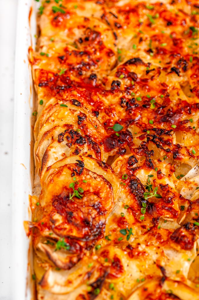 Root Vegetable Gratin in white casserole dish on white marble close up