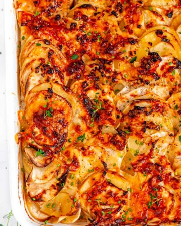 Root Vegetable Gratin in white casserole dish on white marble