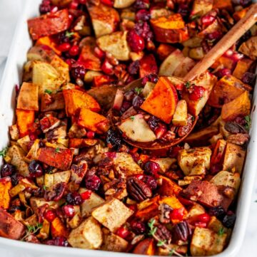 Sweet Potato Cranberry Casserole in white baking dish with wooden spoon on marble