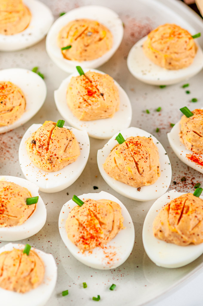 Thanksgiving Pumpkin Deviled Eggs with chives on gray plate close up