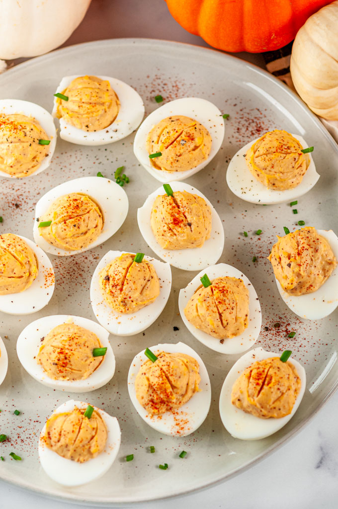 Thanksgiving Pumpkin Deviled Eggs with chives on gray plate and white marble
