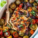 Easy Mediterranean Baked Feta in small blue baking dish with cherry tomatoes and kalamata olives