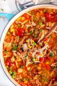 Loaded Chicken Hominy Soup in blue le creuset dutch oven with wood spoon
