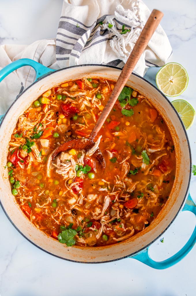 Loaded Chicken Hominy Soup in blue le creuset dutch oven with wooden spoon and limes on white marble