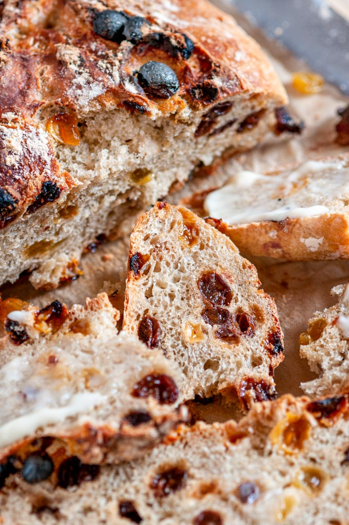 No Knead Cinnamon Raisin Bread sliced with butter on parchment paper