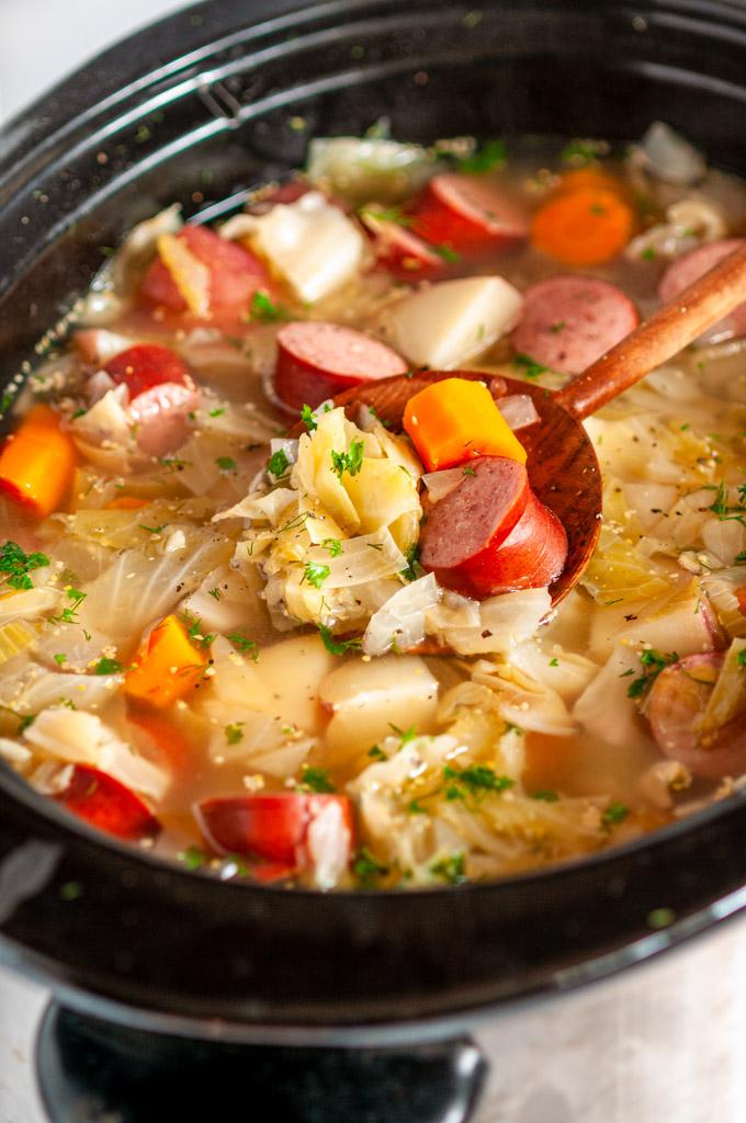 Slow Cooker Kielbasa Cabbage Stew in crock pot with wooden spoon