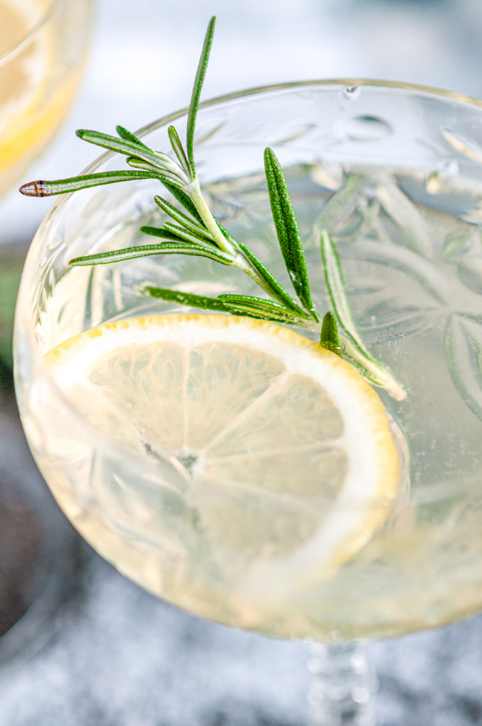Sparkling Elderflower Gin Cocktail in crystal glass with rosemary and lemon slices close up