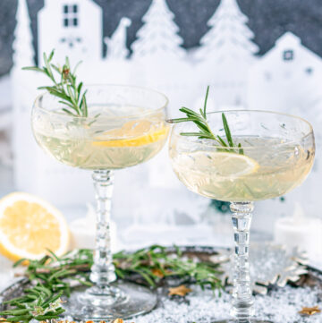 Sparkling Elderflower Gin Cocktail in crystal glasses with rosemary, lemon slices, and paper holiday village in background